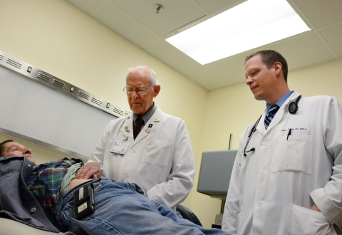 Dr. Hilliard Seigler examines a Veteran as Physician's Assistant Kevin Dendy looks on.  Seigler is VA's oldest Veteran employee