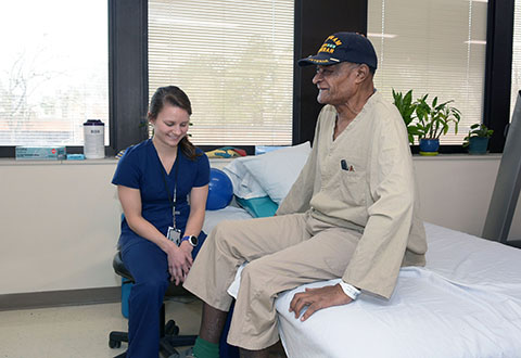 A Durham VAMC Provider works with a geriatric patient at bedside